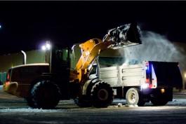 A front-end loader loading salt into a dump truck.